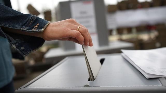 Purtret d'ina dunna che metta ina brev da votaziun en l'urna.