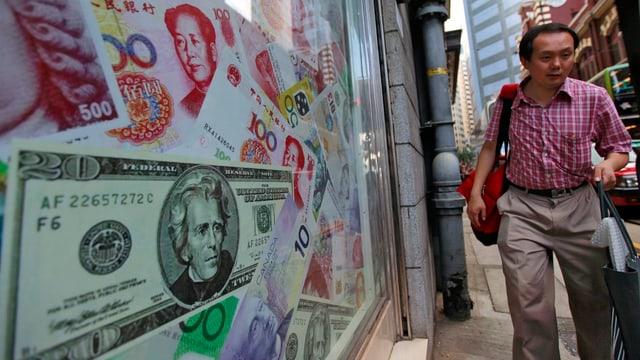 In Hongkong läuft ein Mann an einer Sammlung überdimensiionierter Geldscheine vorbei.