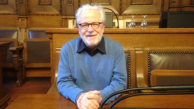 Thomas Dähler sitzt im Grossrats-Saal, verschränkt die Hände und schaut freundlich in die Kamera. Im Saal ist sind Möbel und Wändeaus Holz.