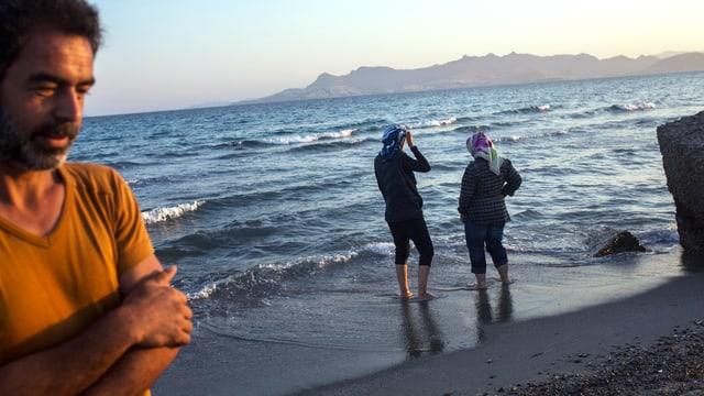 Ein Mann steht am Meer, am Hintergrund laufen zwei Frauen am Strand.