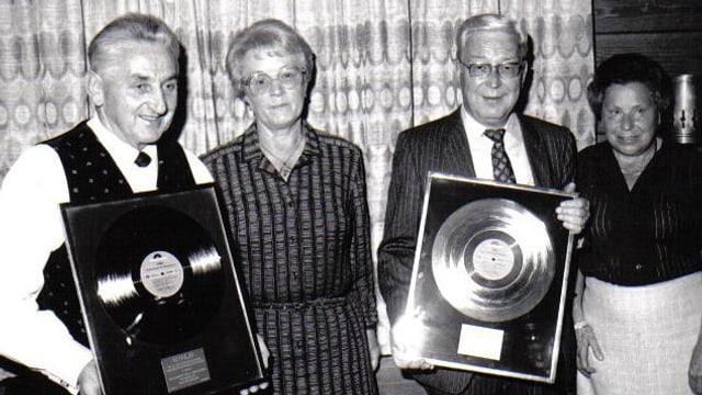 Fotografie in schwarz-weiss, nebst Walter Hofer mit der Goldenen Schallplatte sind noch drei andere Personen auf dem Bild.