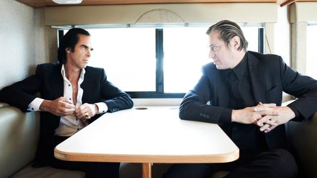 Nick Cave und Blixa Bargeld an einem Tisch