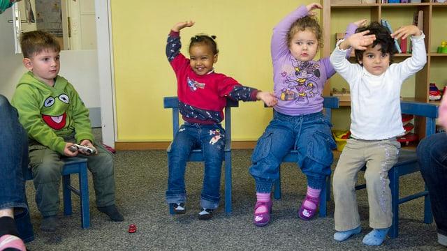 Kinder sitzen auf kleinen Stühlen und halten ihre Arme in die Luft.
