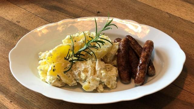 Ein Teller mit Kartoffelsalat und gebratenen Würsten.Garniert mit einem Rosmarinzweig.