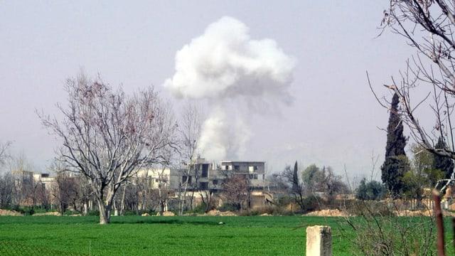 Ein Haus in der Ferne, dahinter eine aufsteigende Rauchwolke nach einem Bombeneinschlag.