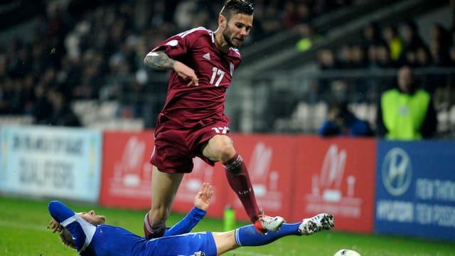Edgars Gauracs überspringt in einem Länderspiel mit Lettland einen Gegenspieler.