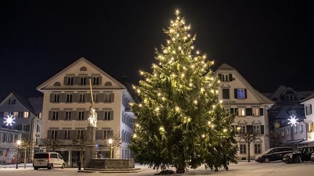 Grosser Weihnachtsbaum auf dem verschneiten Dorfplatz in Stans.