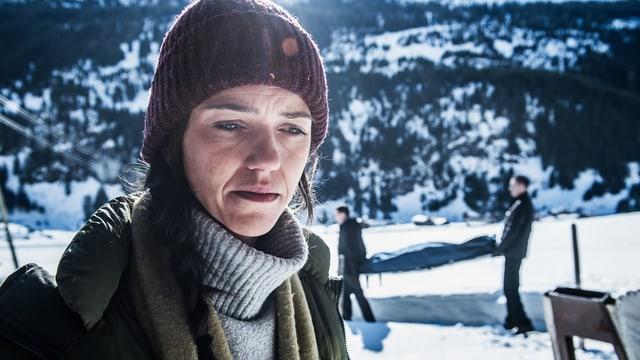 In der verschneiten Landschaft ist Kommissarin Rosa Wilder ist im Vordergrund zu sehen, im Hintergrund wird eine Leiche abtransportiert.