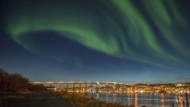 Nordlichter über einer Stadt mit Brücke über das Wasser.