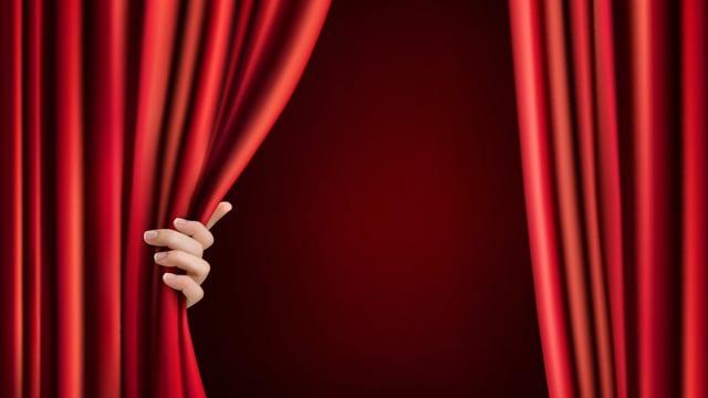 Hand öffnet roten Vorhang