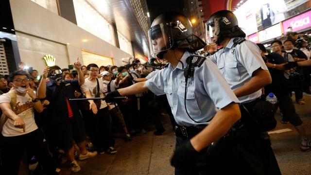 Polizisten versuchen, Demonstranten zurückzuhalten.