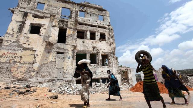 Menschen vor einem zerstörten Haus in Soamlias Hauptstadt Mogadischu