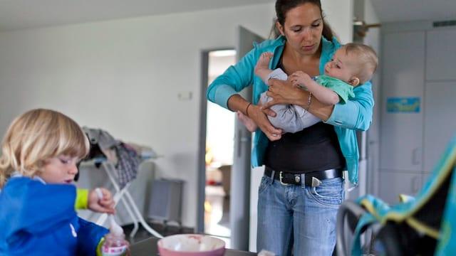 Eine Mutter hält ein Kind im Arm und ein Buc sitzt am Tisch.