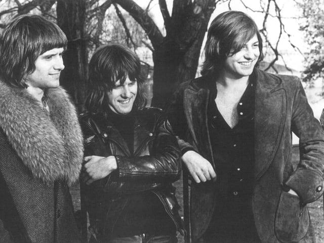 Die Band ELP mit Mäntel und Lederjacken und langen Haaren.