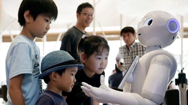 Uffants sa dattan giu cun in roboter umanuid.
