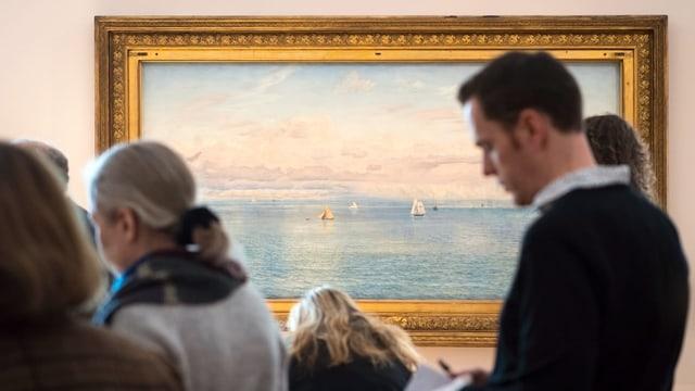 Szene aus der Ausstellung. Menschen stehen vor dem Gemälde «Das britische Reich» von John Bratt. Es zeigt Wasser, Schiffe und Wolken.