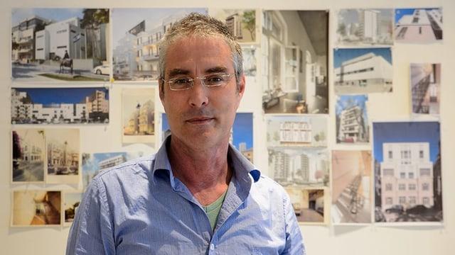 Ein mann mit hellblauem Hemd, hinter ihm an der Wand hängen Fotos von Gebäuden.
