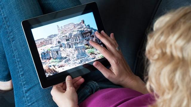 Eine sitzende Frau betrachtet auf ihrem Tablet ein Foto.