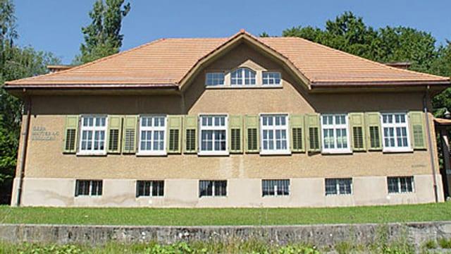 Das GEbäude von aussen betrachtet: Es hat ein klassisches Ziegeldach, mit einem Dachstock und drei kleinen Fenstern, der 1. STock hat 6 hohe Fenster mit grünen Fensterläden. Die Fenster des Parterres sind deutlich kleiner und vergittert.