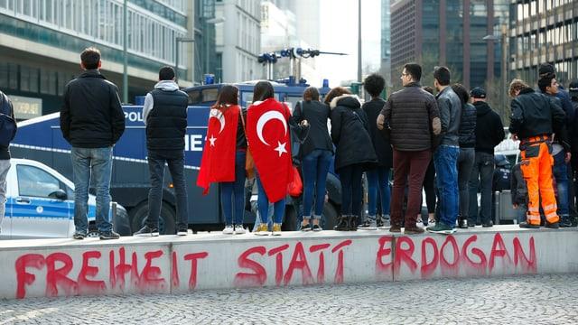 """Menschen stehen in einer Strasse, auf einer Mauer steht """"Freiheit statt Erdogan""""."""