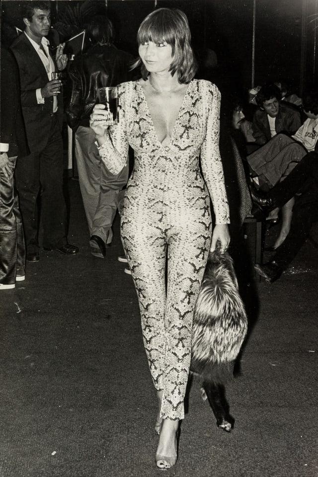 Schwarz-Weiss-Foto: EIne Frau in einem Schlangen-Catsuit.