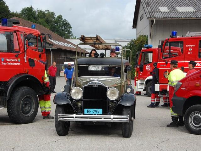 Altes Feuerwehrauto fährt durch Spalier von neuen Fahrzeugen.