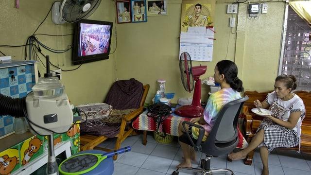 Zwei Frauen in einem ärmlichen Raum schauen Fernsehen.