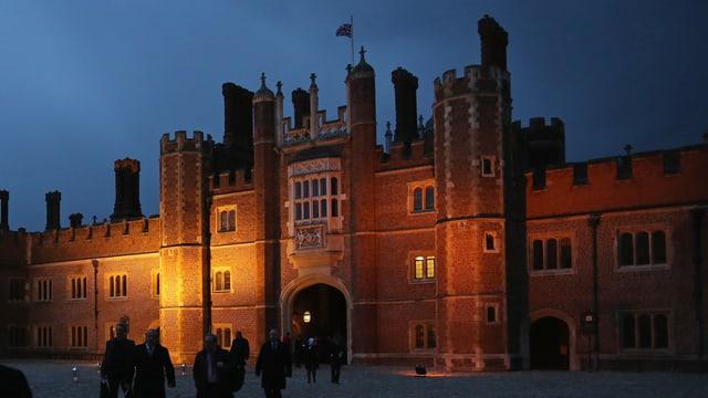 Schloss aus rotem Backstein bei Nacht, von einer gleblichen Lampe beleuchtet.