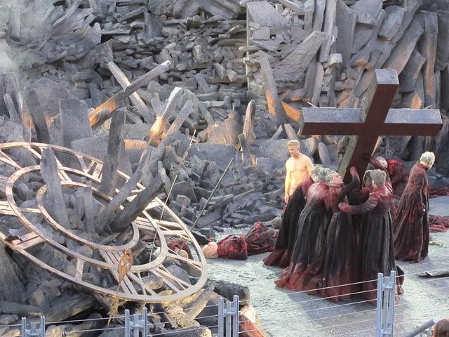 Mehrere Personen halten an grosses Kreuz fest. Im Hintergrund sind Schutt und Asche zu erkennen.