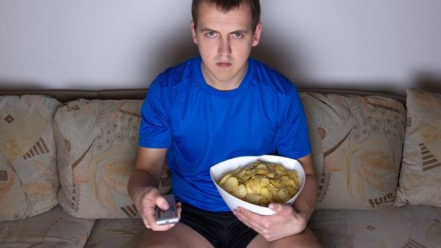 Ein junger Mann sitzt mit Kartoffelchips und Fernbedienung vor dem Fernsehgerät.