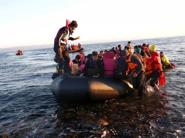 Ein Gummiboot voller Menschen im knietiefen Wasser, Helfer stehen bereit.