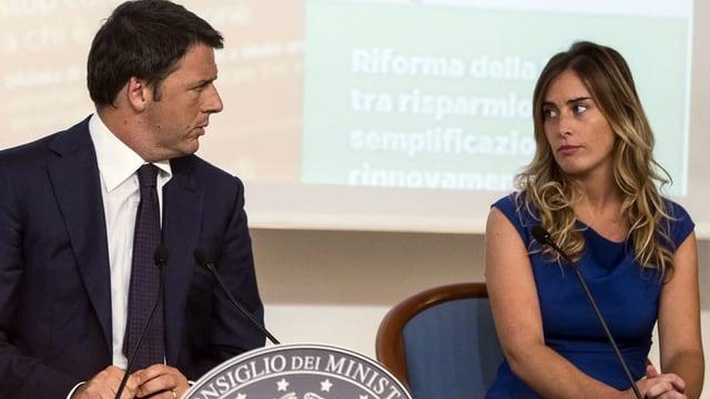 Renzi sitzt neben Boschi, die beiden sehen sich fragend an.