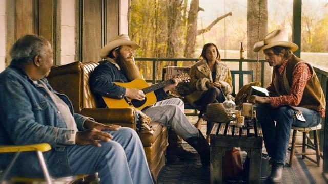 Ein Mann spielt auf einer Terrasse Gitarre, zwei Männer und eine Frau hören zu