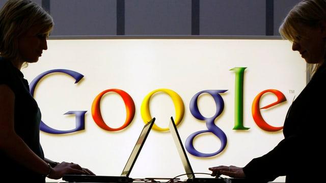 Silhouetten von zwei Frauen mit Laptops, die vor einem Google-Logo stehen
