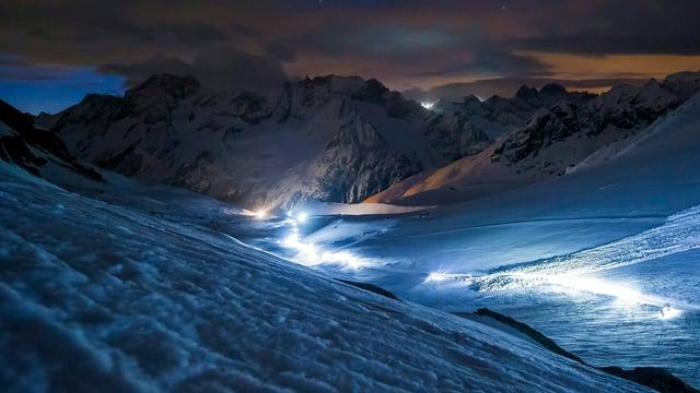 Offenes Hochtal mit Leuchtspur der Sportler. Im Hintergrund schorffe Berge, im Vordergrung viel Schnee. Alles im diffusen Licht der Nacht.