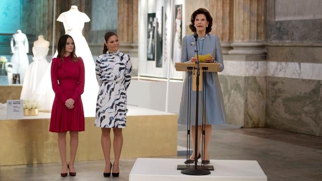 Königin SIlbia in einem Grauen Kleid hält eine Rede. Hinter ihr stehen Victoria in einem schwarzweissen kleid und Sofia in einem roten Kleitd.