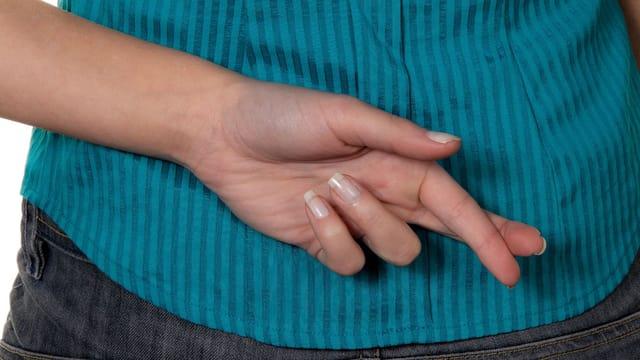 Eine Frau kreuzt hinter ihrem Rücken ihre Finger