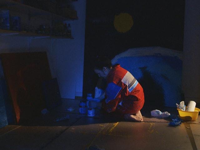 Die Künstlerin knieht im Dunklen am Boden, neben ihr Bilder und Maluntensilien.