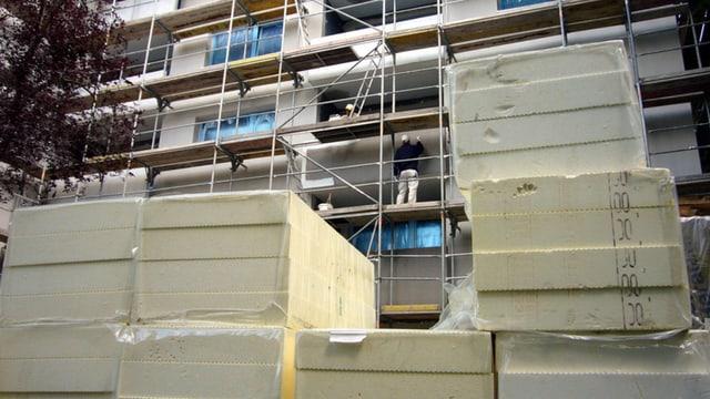 Eingerüstetes Gebäude mit Isolationsmaterial davor und Bauarbeiter am Arbeiten.