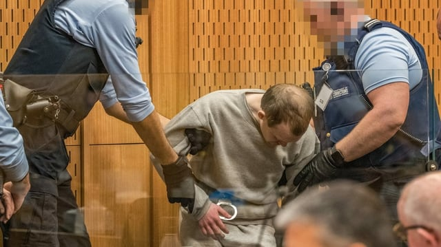 Mann wird von Polizisten in Handschellen abgeführt.