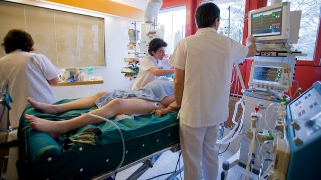 Mehrere Pflegende in einem Spitalzimmer.