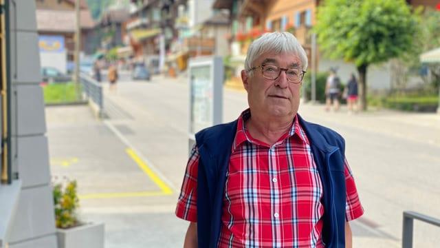 Mann steht in rot-blau-kariertem Hemd an einer Dorfstrasse