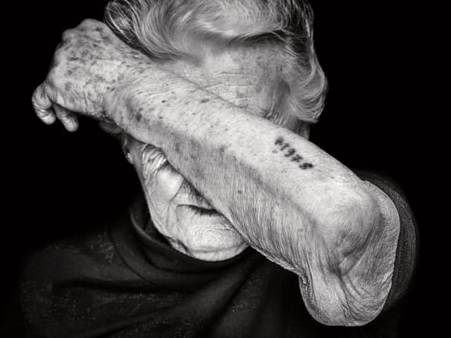 Alte Frau, die Hand vor Gesicht hält. Am Arm ist eine Nummer eintätowiert.