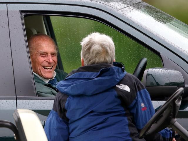 Prinz Philip sitzt in seinem stehenden Auto am Steuer und spricht über die heruntergelassene Fensterscheibe zu einem Passanten.