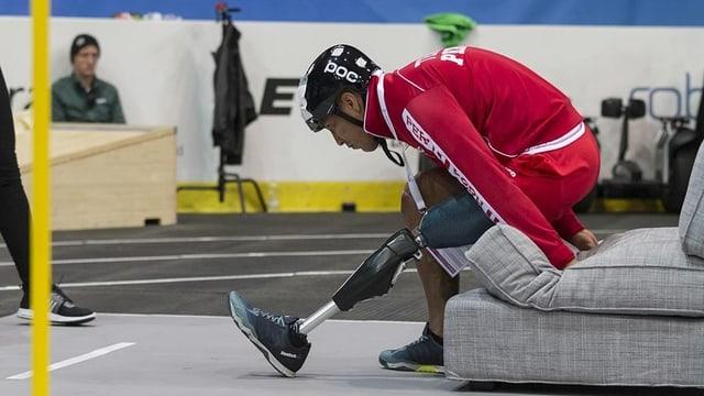 Ein Mann mit einer Beinprothese steht auf.