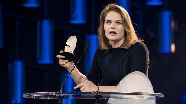 Hazel Brugger steht mit einer Trophäe in der Hand an einem Glastisch.