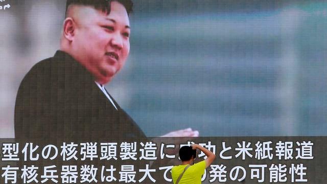 Ein Passant steht vor einem grossen Fernsehschirm mit dem Bild von Kim Jong-un.
