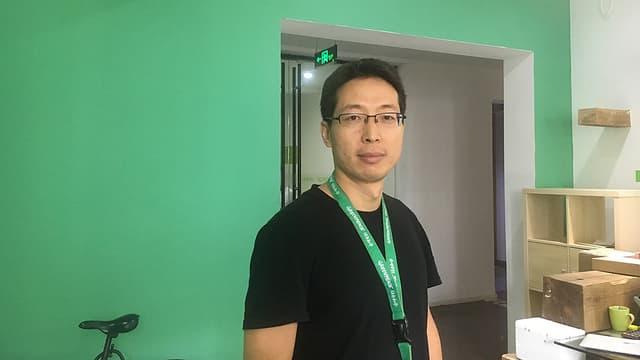 Mann mit Brille vor grüner Wand.