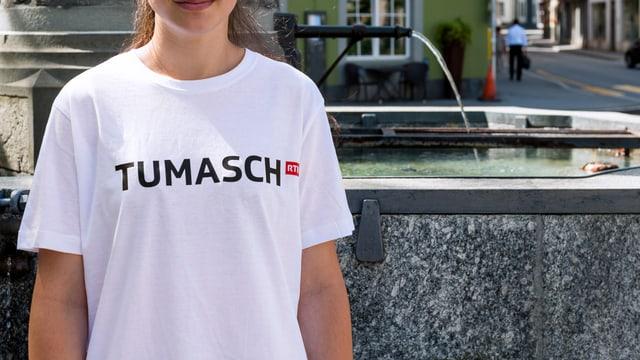 Ina giuvna cun il t-shirt da Tumasch avant la funtauna sper la plazza dal teater a Cuira. Ins na vesa betg la fatscha da la giuvna.