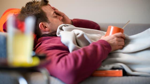 Person liegt mit Grippe auf Sofa.